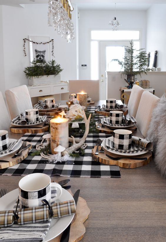a rustic Christmas table with a buffalo check runner, mugs, napkins, antlers, a candle in a tree stump and some striped napkins