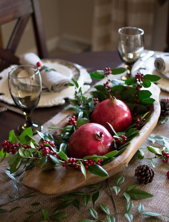 a rustic Christmas table with a burlap runner, greenery, berries, pinecones and a dough bowl with pomegranates and berries