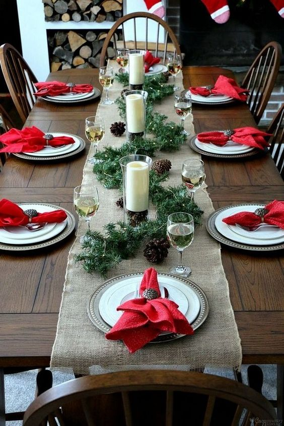 a rustic Christmas table with a burlap runner, metal chargers, red napkins, an evergreen runner, pinecones and candles