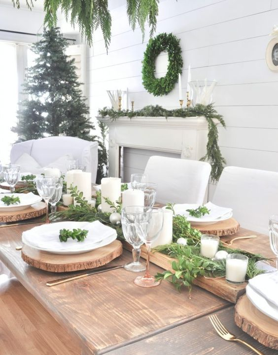 a rustic Christmas tablescape with an uncovered table, a greenery runner with candles, wood slice placemats