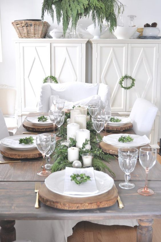 a rustic Christmas tablescape with wood slice chargers, an evergreen runner, candles and ornaments plus some greenery