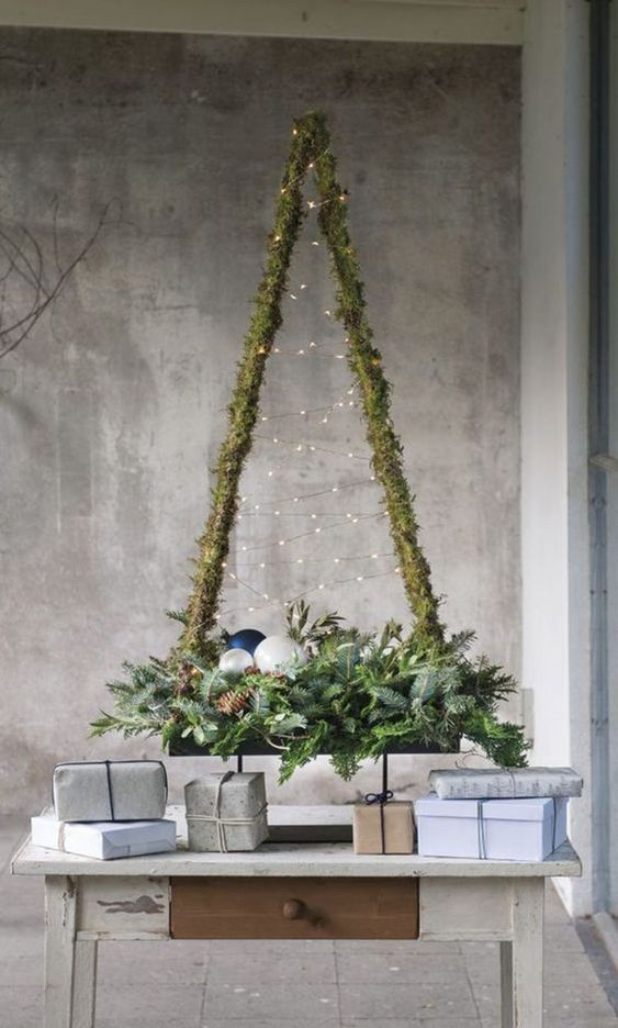 a rustic Christmas tree wrapped wiht moss, with lights and evergreens, pinecones, ornaments for a cozy and modern feel