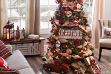 a rustic vintage Christmas tree withburlap ribbons, colorful lights, a hat on top, a toytruck and gift boxes