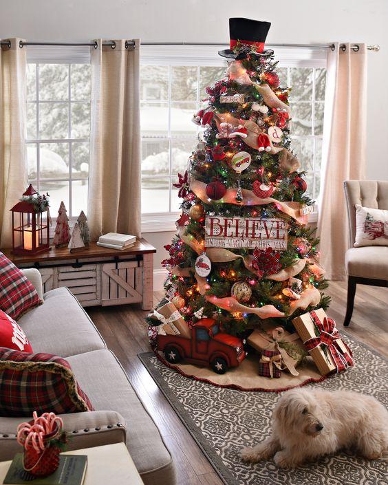 un arbre de Noël vintage rustique avec des rubans de jute, des lumières colorées, un chapeau sur le dessus, un camion de jouets et des coffrets cadeaux