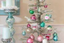 a silver tabletop Christmas tree with bright pink and turquoise ornaments looks cute and very chic
