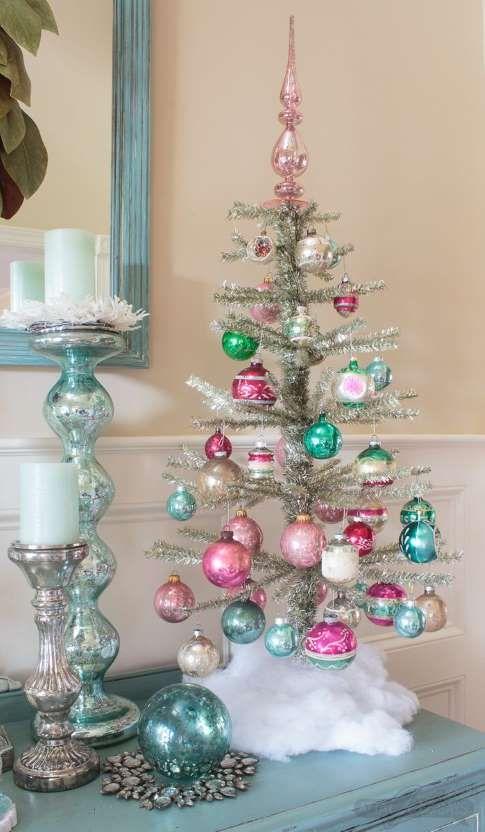 un arbre de Noël de table en argent avec des ornements rose vif et turquoise est mignon et très chic