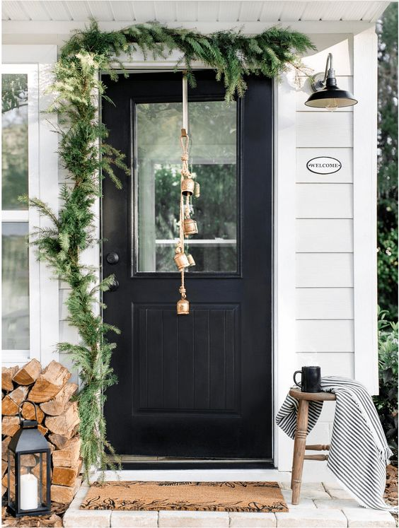 a simple and natural Christmas porch with evergreens, firewood, candle lanterns and bells on the door is very cool