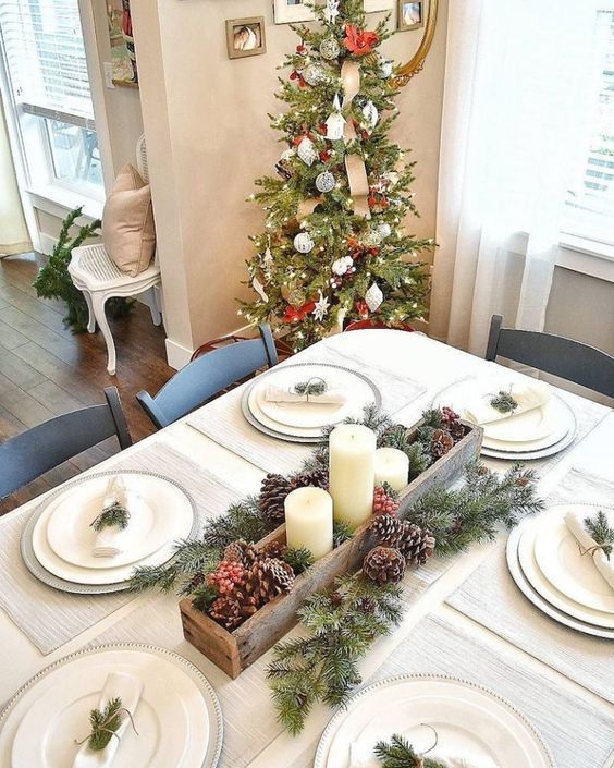 a simple neutral Christmas tablescape with silver chargers, white plates, evergreens and pinecones, berries and candles