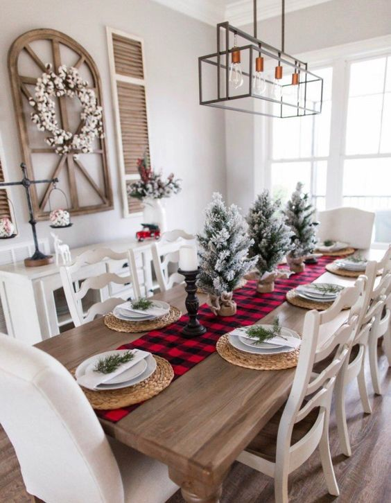 a simple rustic Christmas table with a plaid runner, woven placemats, snowy Christmas trees and evergreens