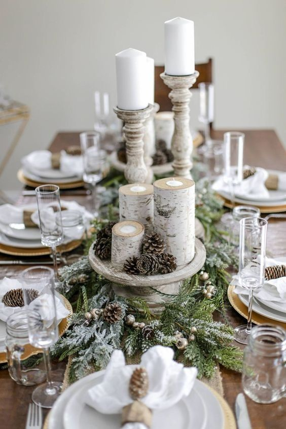 a snowt rustic Christmas table with a flocked evergreen runner, pinecones, branch candleholders, pinecone napkin rings