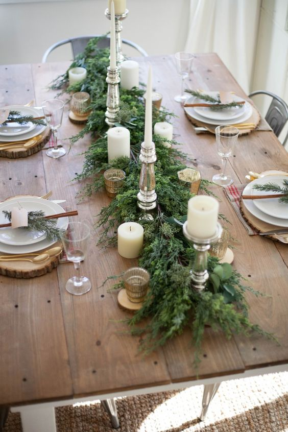 a stylish rustic Christmas table with an evergreen runner, candles, wooden placemats, cinnamon sticks and gold cutlery