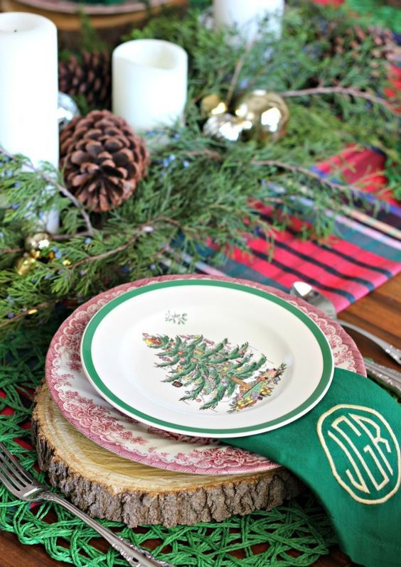 a traditional Christmas table with wooden slice chargers, printed plates, evergreens and pinecones plus candles and green napkins