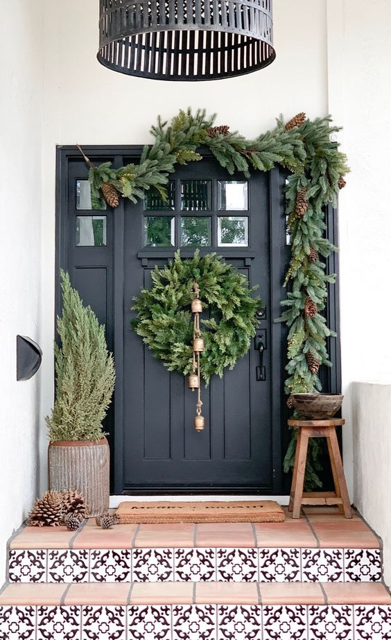 a very natural Christmas porch with a tree, pinecones, an evergreen wreath with bells and an evergreen garland with pinecones