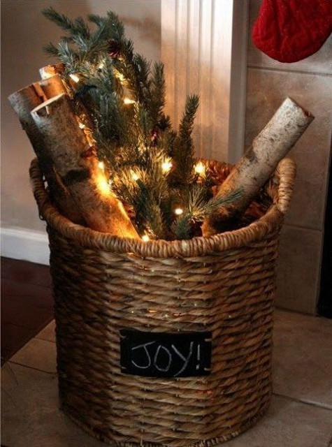 a vine basket with firewood, lights and evergreens is a cool decoration for both indoors and outdoors