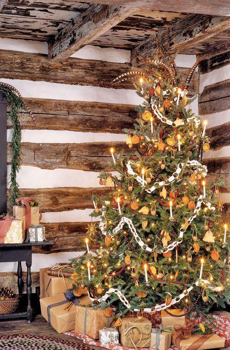 un arbre de Noël vintage décoré de lumières, de tranches d'agrumes, d'étoiles, de guirlandes de canneberges, de chaînes en papier et d'autres trucs