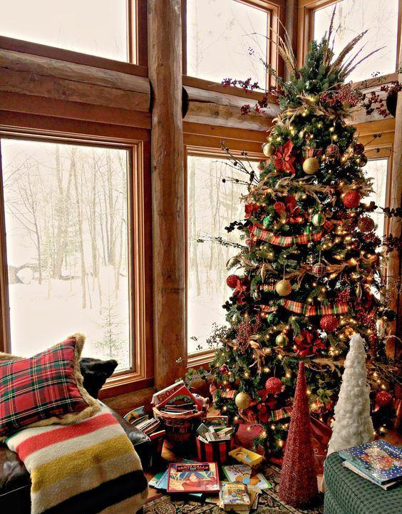 un arbre de Noël vintage avec des lumières, des ornements rouges, or et verts, des brindilles, des baies et des herbes