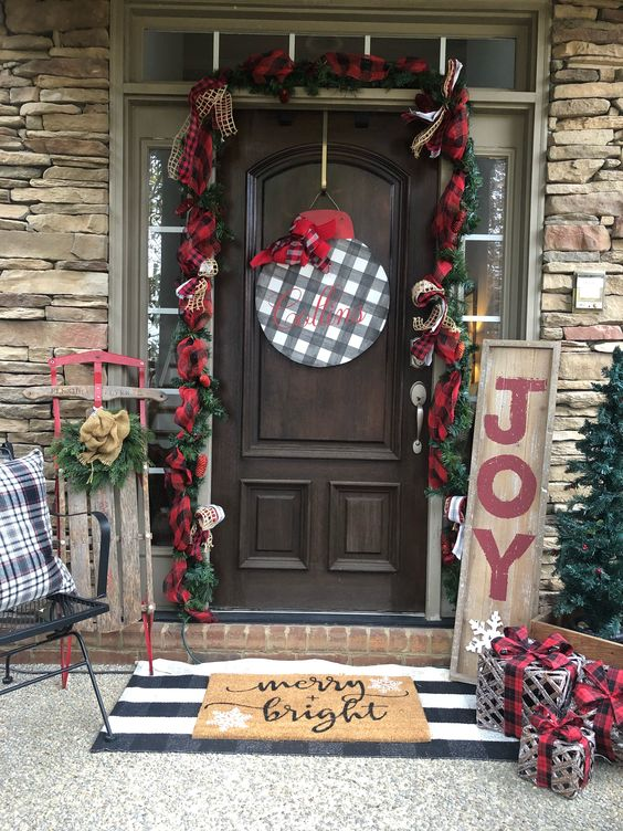 a vintage farmhouse Christmas porch with plaid ribbons, evergreens, a plaid sign, vine gifts and pillows plus a decorated sleigh