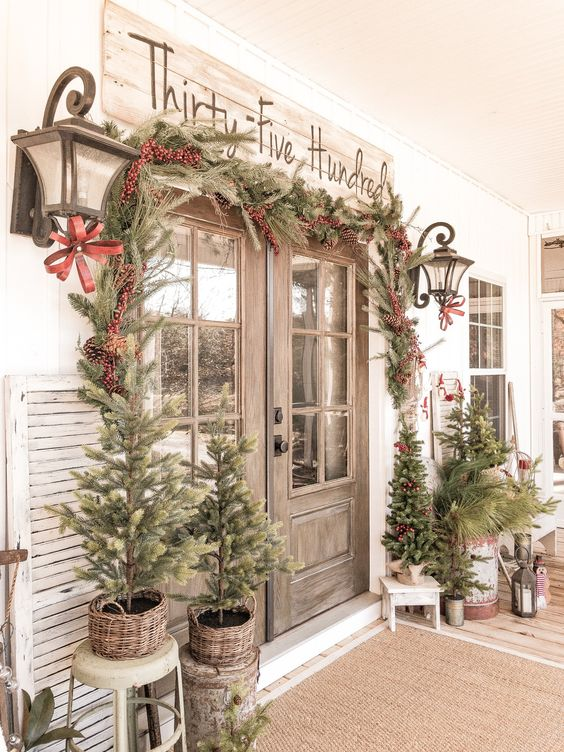 a vintage rustic Christmas porch with an evergreen garland with berries and pinecones, mini trees that aren't decorated and lanterns