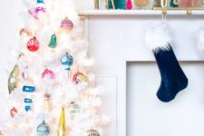 a white Christmas tree decorated with colorful vintage Christmas ornaments and a topper is a stylish and chic idea