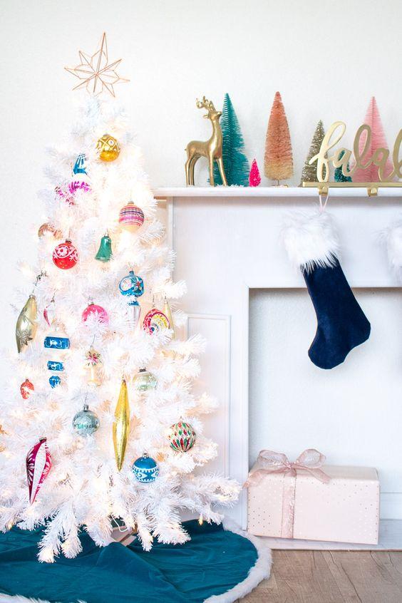 un arbre de Noël blanc décoré avec des ornements de Noël vintage colorés et un haut de forme est une idée élégante et chic