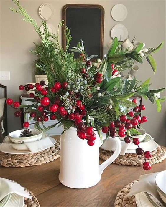 a white jug with lots of textural greenery, berries and fruits, woven placemats and printed porcelain for a rustic Christmas