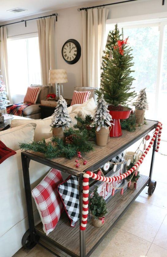a wooden cart with pompom garlands, plaid pillows. flocked trees in pits and a large tree on a red stand for Christmas
