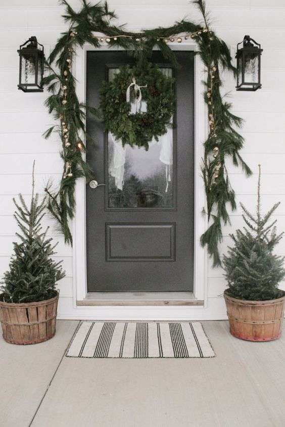 a woodland Christmas porch with mini trees in wooden buckets, a fir garland with metallic ornaments and a fir wreath on the foor is very cool
