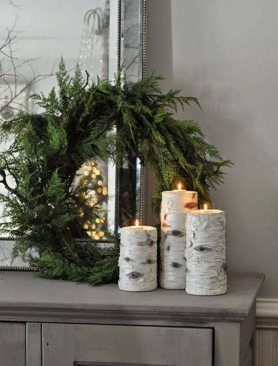 an evergreen wreath with tree stump candleholders with candles are a nice Christmas combo