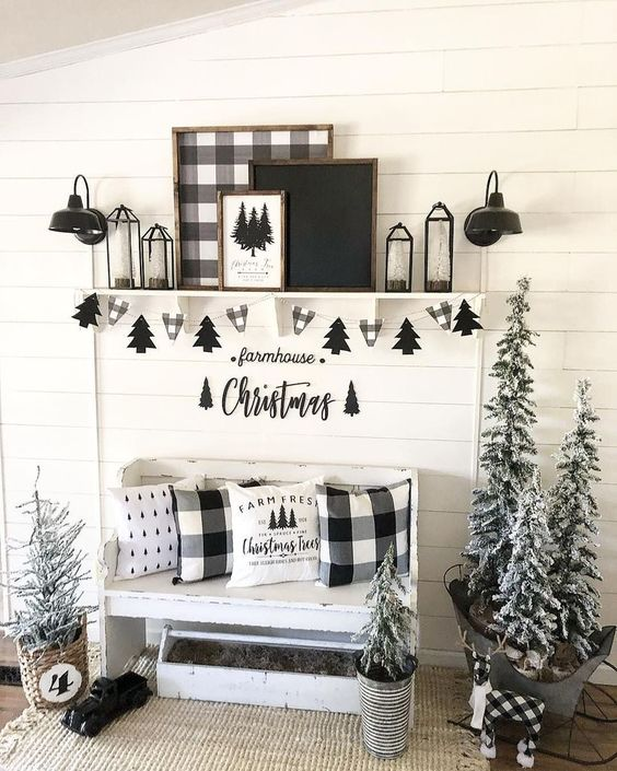 black and white farmhouse entryway with plaid pillows, buntings, artworks and flocked Christmas trees in buckets and baskets
