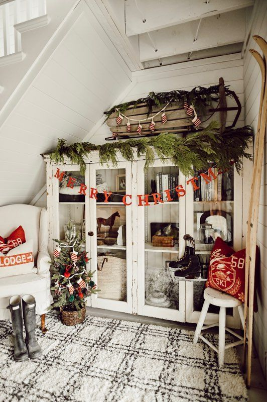 evergreens, a sleigh with mitten garlands, red letter garlands, a mini tree in a basket and red pillows