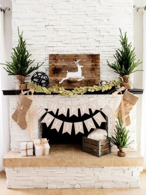 rustic fireplace styling with Christmas trees wrapped in burlap, burlap stockings, a paper garland, a fabric leaf one and a deer sign