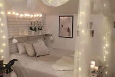 sheer fabric canopy with lights and lights over the bed for a chic and romantic look