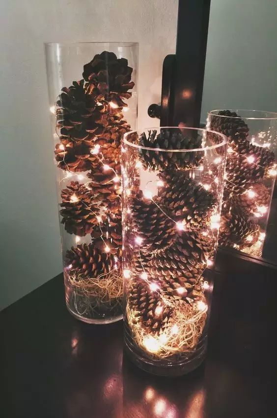 tall vases with pinecones and lights are a great rustic Christmas decoration or centerpiece