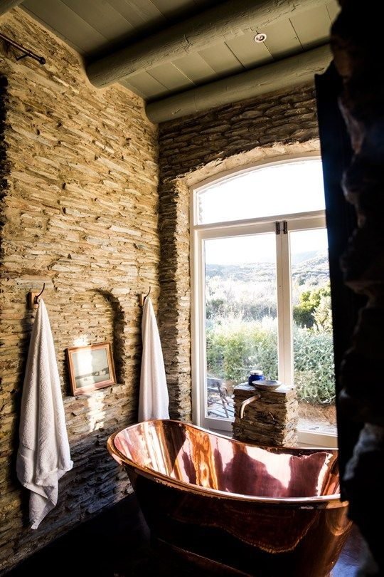 a beautiful bathroom with stone walls, a copper bathtub and towels plus a gorgeous view featured