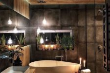 a beautiful moody bathroom clad with wood and with dark tiles, with a chic bathtub, a floating wood slab vanity and candles around