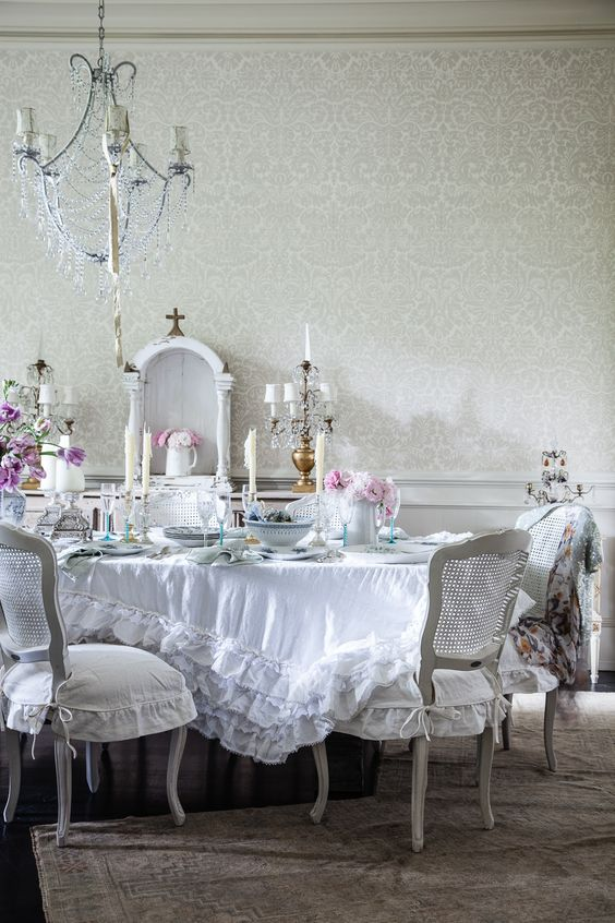 a beautiful shabby chic dining room with a crystal chandelier, white furniture, a ruffle tablecloth and blooms