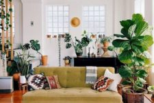 a boho meets mid-century modern living room with prints, a mustard sofa, potted plants and rattan and wicker touches