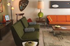 a boho mid-century modern living room with green, rust, neutral items, lamps and quirky artworks