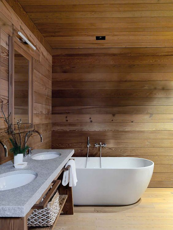 a chalet bathroom clad with wood, with an oval tub, a wooden vanity with a double sink is very simple and very inviting