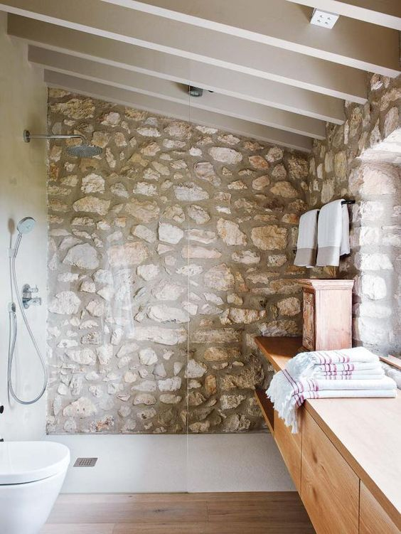 a chic attic bathroom with a rough stone wall, a sleke wooden vanity and enough natural light incoming