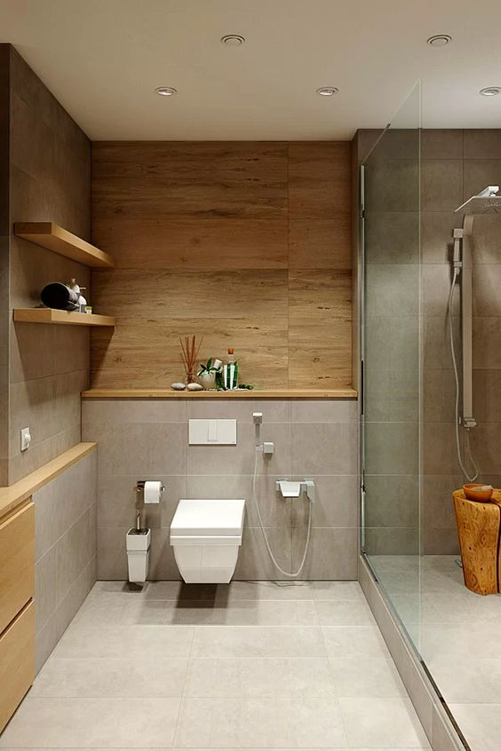 a chic minimalist bathroom clad with grey tiles and wood, with a shower space and a tree stump, open shelves for storage