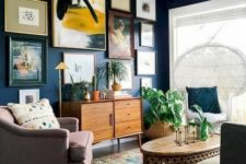 a chic navy living room with touches of yellow, a fringe rug, mismatching furniture and a peacock chair plus a gallery wall