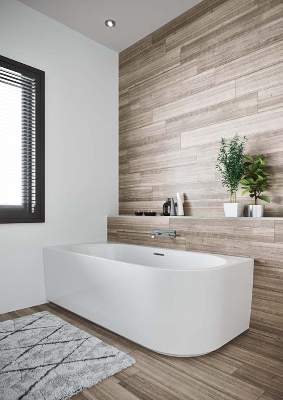 a clean contemporary bathroom done with laminate, with a chic bathtub and a raised shelf over it, with a window and a printed rug