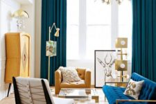 a colorful mid-century modern space with a sunburst chandelier, navy and yeloow items, metallic touches and prints