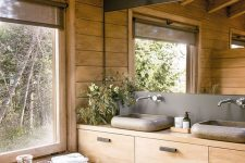 a contemporary bathroom fully clad with wood, with a large mirror, a wooden vanity and a window for a cool view