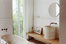 a contemporary bathroom with a wooden floor, a wooden tub, a wooden vanity and a stone sink plus white subway tiles