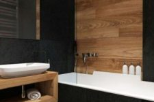 a contemporary bathroom with black tiles, light stained wood, an open wooden vanity, a bathtub with blakc tiles is chic