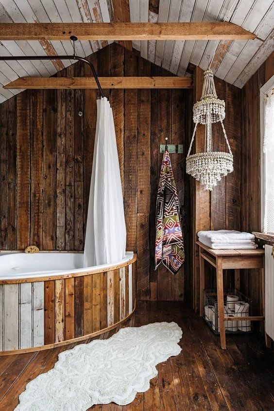 a creative bathroom clad with dark stained rough wood, with a bathtub clad with wood, beaded chandeliers and printed textiles
