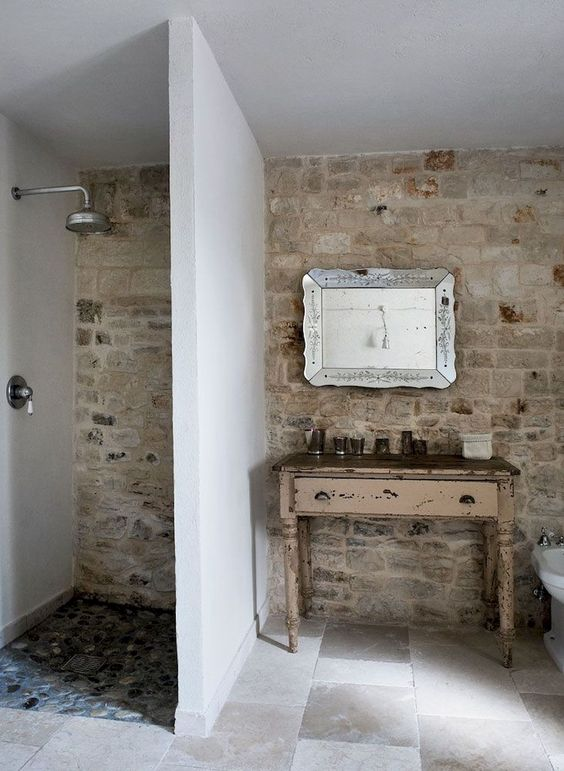 a farmhouse bathroom with a stone wall, tiled floor, a shaby chic vanity and a gorgeous refined mirror