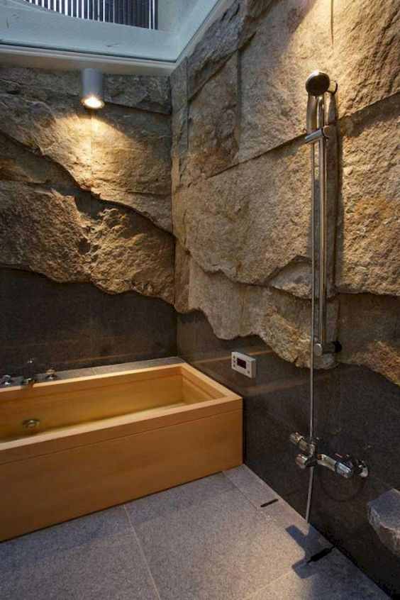a gorgeous contemporary bathroom done with rough stone walls covered with glass and a wooden bathtub